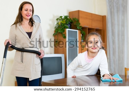 Mother and daughter cleaning the living room - stock photo