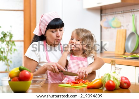 mother and daughter cooking and cutting vegetables on kitchen - stock photo