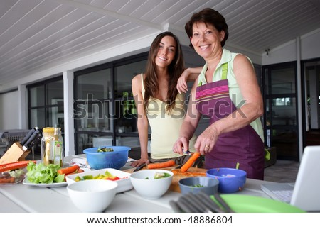 Mother and daughter cooking at home - stock photo