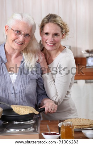 Mother and daughter cooking crepes together - stock photo