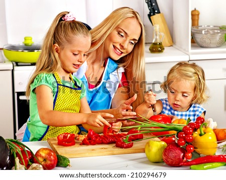 Mother and daughter cooking food at kitchen. - stock photo