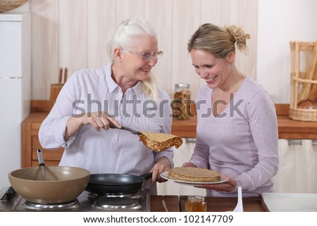 Mother and daughter cooking pancakes - stock photo