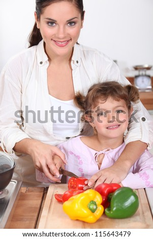 Mother and daughter cooking together. - stock photo