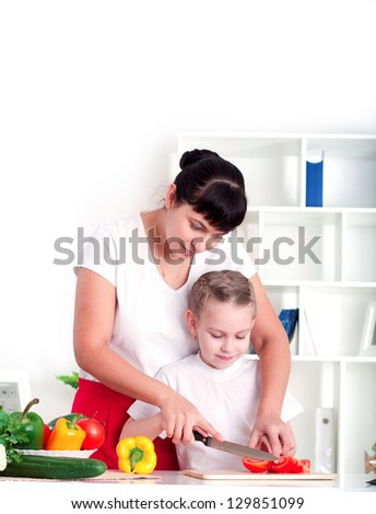 Mother and daughter cooking vegetable salad together - stock photo