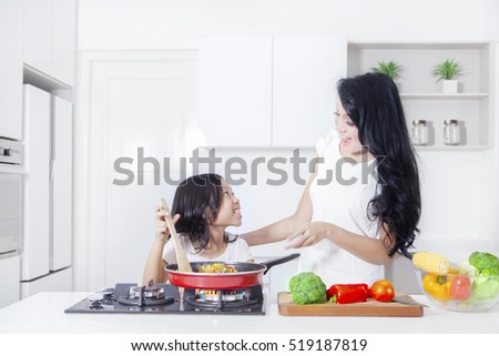 Mother and daughter cooking vegetable together in the kitchen