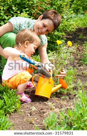 Mother and daughter cultivating the garden - stock photo
