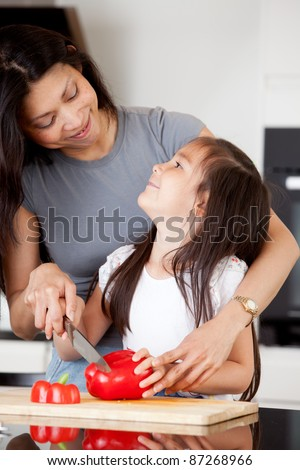 Mother and daughter cutting vegetables together - stock photo