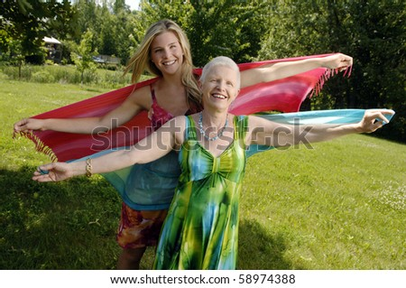 Mother and daughter dance and smile in the backyard. - stock photo