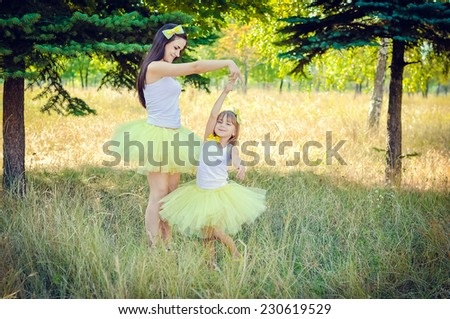 Mother and daughter dancing in the park - stock photo