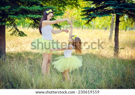 Mother and daughter dancing in the park