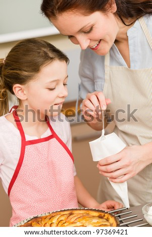 Mother and daughter decorating apple pie with sugar icing - stock photo