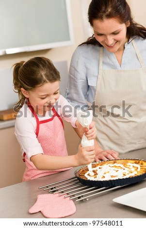 Mother and daughter decorating apple pie with whipped cream