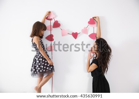 Mother and daughter decorating the house with heart shaped garland. Concept of family values, happy living, celebrating the holidays, preparing for valentines day - stock photo
