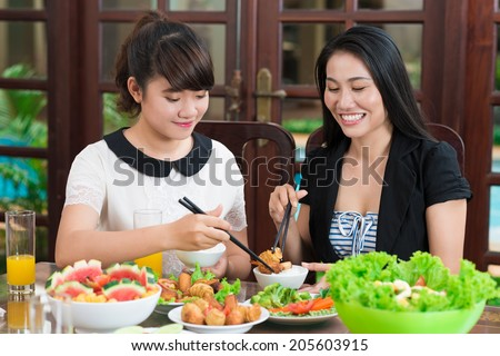 Mother and daughter dipping meat pieces into sauce - stock photo