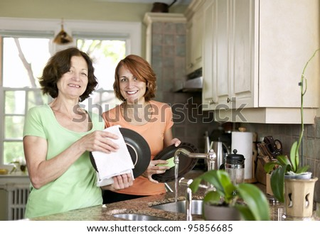 Mother and daughter doing dishes in kitchen at home - stock photo