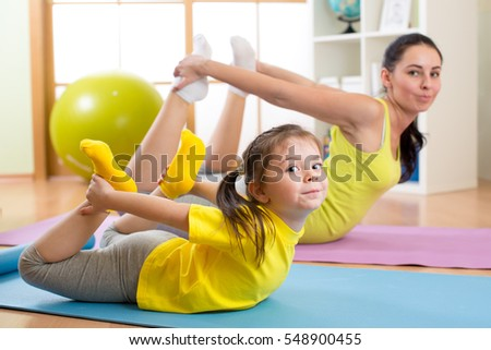 Mother and daughter doing fitness exercises on rug at home