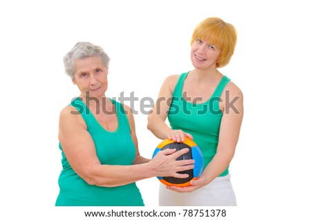mother and daughter doing gymnastics with ball on white background - stock photo