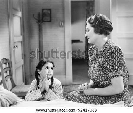 Mother and daughter doing the evening prayer in the child's bed room - stock photo