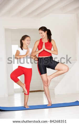Mother and daughter doing yoga - stock photo