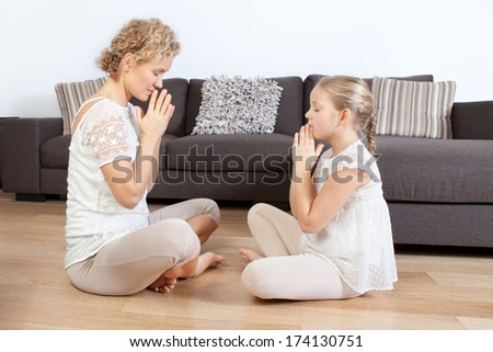 Mother and daughter doing yoga exercises  - stock photo