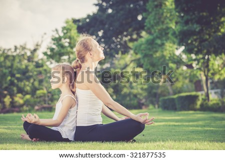Mother and daughter doing yoga exercises on grass in the park at the day time