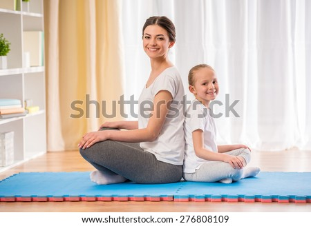 Mother and daughter doing yoga exercises on rug at home.