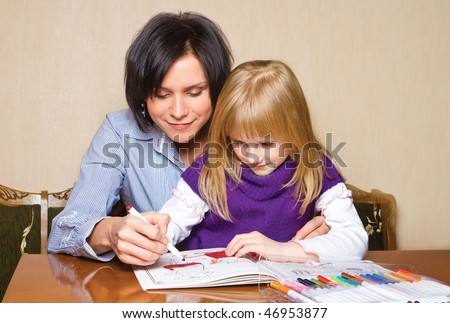 Mother and daughter drawing in the book