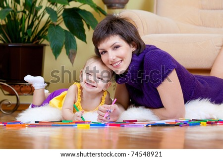 Mother and daughter drawing picture - stock photo