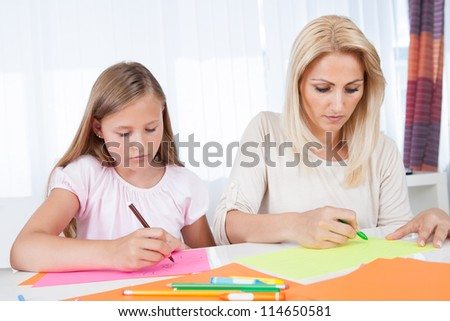 Mother And Daughter Drawing Together With Colorful Pencils And Crayons At Home - stock photo