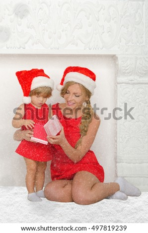 mother and daughter dressed as Santa with gift and snow on gray background