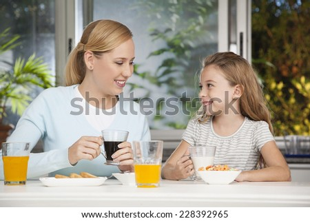 Mother and daughter drinking fresh juice