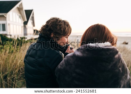 Mother and Daughter Drinking from Coffee Cups at Sunset at the Beach looking at sunset behind shot - stock photo