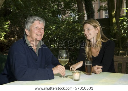 Mother and daughter drinking in the garden - stock photo