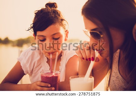 Mother and daughter drinking juice at cafe - stock photo