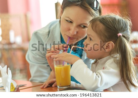 Mother and daughter drinking juice in cafe - stock photo