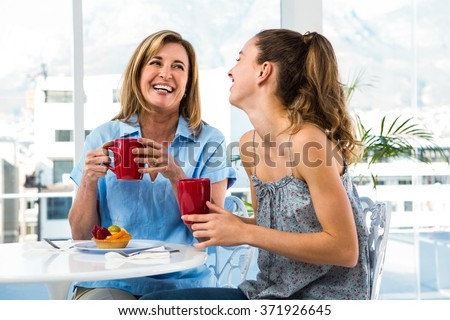 Mother and daughter eat breakfast at home in the kitchen - stock photo