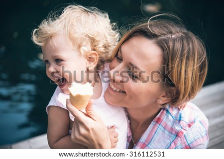 Mother and daughter eat ice-cream during a walk outdoors. Toned image - stock photo