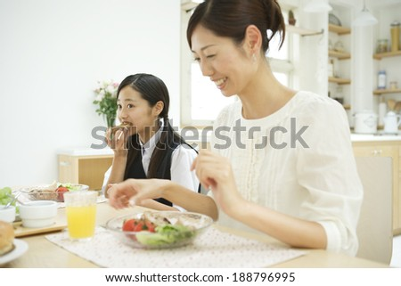 mother and daughter eating breakfast - stock photo