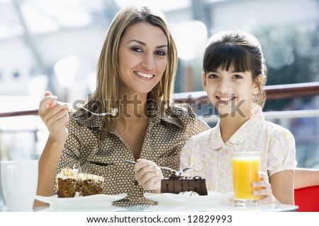 Mother and daughter eating cake in cafe together - stock photo