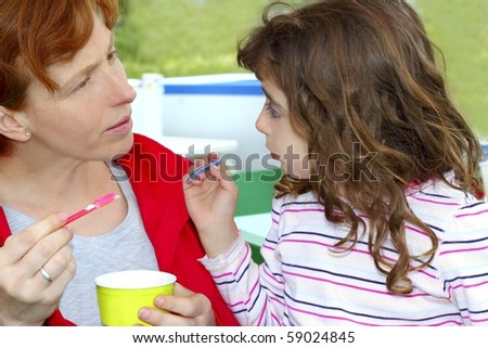mother and daughter eating ice cream talking outdoors - stock photo