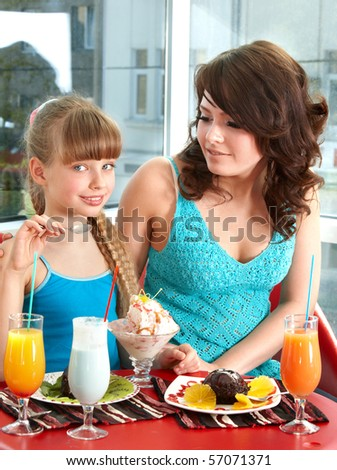 Mother and daughter eating in cafe.