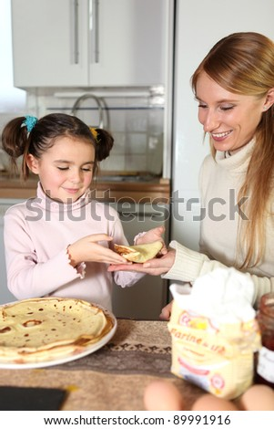 Mother and daughter eating pancakes - stock photo