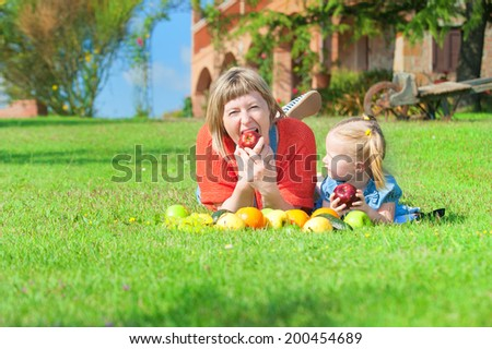 Mother and daughter eating the colorful fruit on green grass
