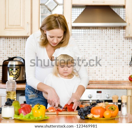 Mother and daughter eating vegetables salad in kitchen