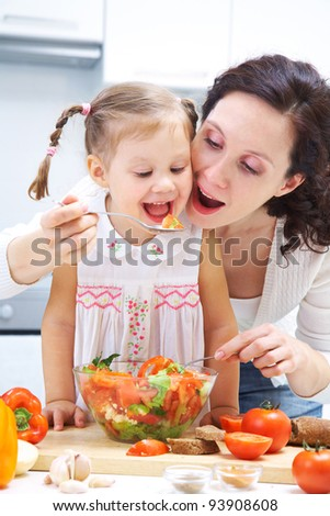 Mother and daughter eating vegetables saladr in kitchen - stock photo