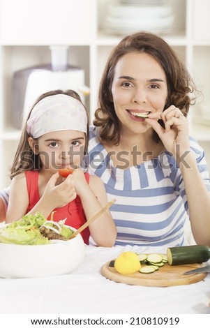 Mother and daughter eating vegetarian food