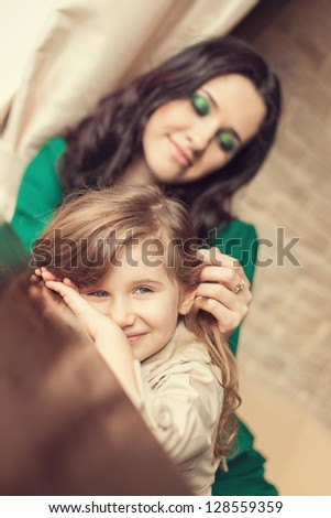 Mother and daughter embracing at home - stock photo