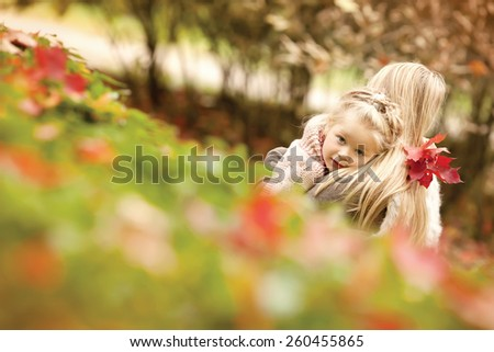 Mother and daughter embracing in the park - stock photo