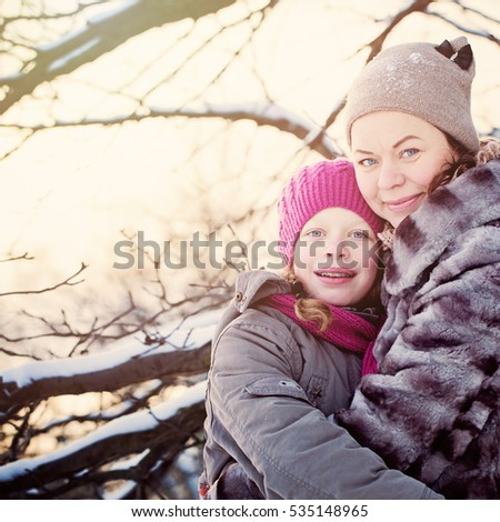 Mother and Daughter Embracing in Winter Day Outdoors. Happy Winter Family.