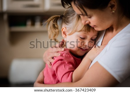 Mother and daughter embracing indoors at home - stock photo
